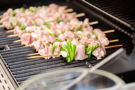 Step by step. Raw chicken yakitori skewers on outdoor gas grill.