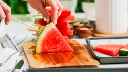 Step by step. Sliding the wood pop stick into the watermelon wage wedge to make watermelon ice pops.