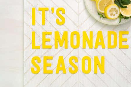 Its lemonade season wood sign with freshly sliced lemons on a wood cutting board.