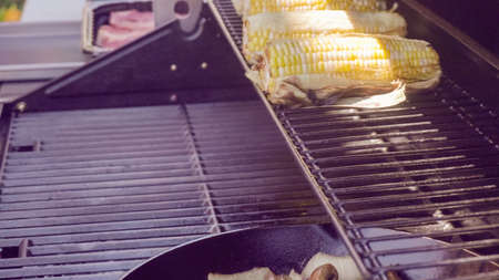 Step by step. Grilling fresh corn on outdoor gas grill. 写真素材