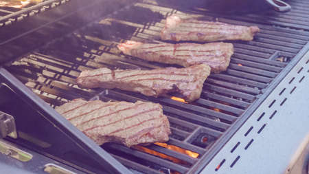 Step by step. Grilling New York strip steak on outdoor gas grill.