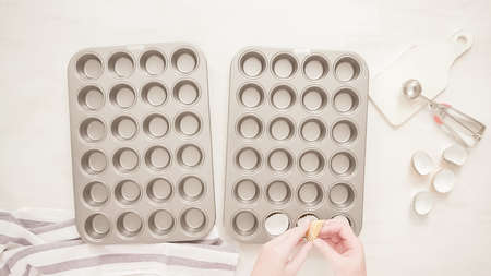 Flat lay. Lining cupcake pan with paper cupcake liners. 免版税图像