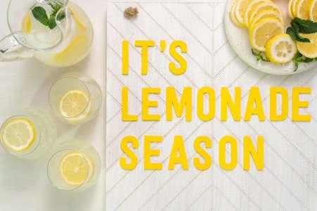 It's lemonade season wood sign with freshly sliced lemons on a wood cutting board.