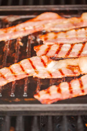 Grilling bacon strips on cast iron griddle in outdoor gas grill. 写真素材