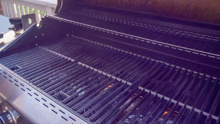 Step by step. Empty cast iron griddle of outdoor gas grill.