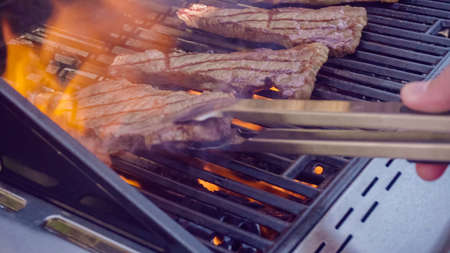 Step by step. Grilling New York strip steak on outdoor gas grill. Archivio Fotografico