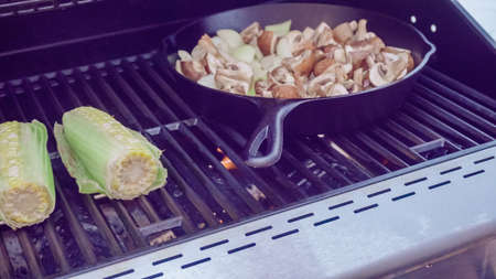 Step by step. Grilled mushrooms and onions in cast iron frying pan on outdoor gas grill. 免版税图像