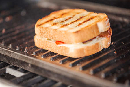 Grilling grilled cheese sandwich with bacon strips and fresh tomato on outdoor gas grill.
