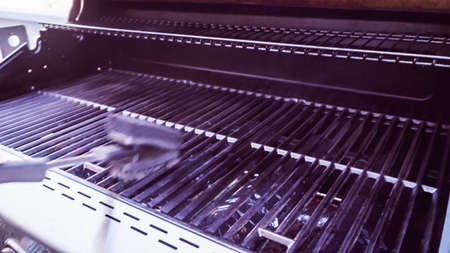 Step by step. Cleaning outdoor gas grill on back patio. Stock Photo