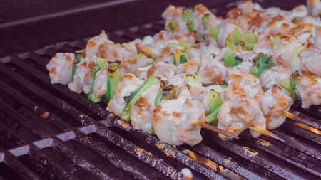 Step by step. Chicken yakitori on a white metal serving tray next to outdoor gas grill.