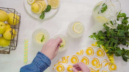 Step by step. Garnishing traditional fresh lemonade with lemon slices and mint. Stock Photo