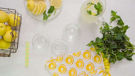 Step by step. Pouring traditional fresh lemonade in glasses.