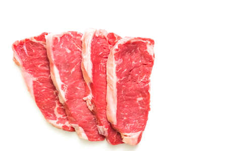Raw New York strip steaks on a white background.