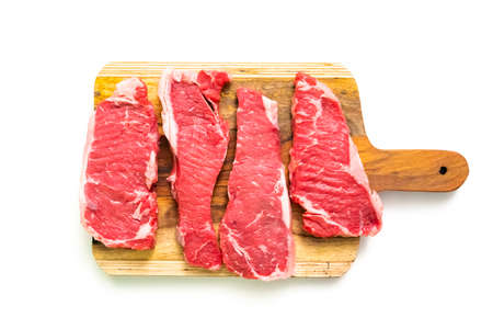 Raw New York strip steaks on a wood cutting board. Zdjęcie Seryjne