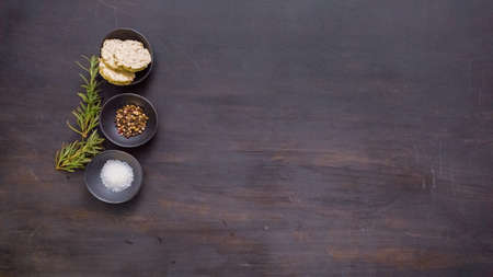 Salt, peppercorns and herb butter in small containers on blacvk wood table.