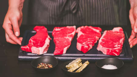 Raw New York strip steaks on a wood cutting board. Stockfoto