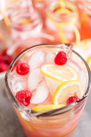 Raspberry lemonade garnished with fresh lemon and raspberries in glass pitcher.