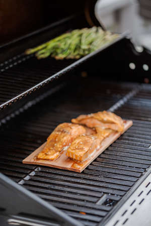 Grilling salmon on cedar plank on outdoor gas grill.
