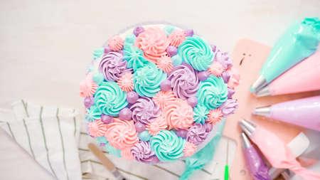 Flach liegen. Pastellfarbene Buttercreme-Rosetten auf einen weißen Kuchen spritzen, um einen Einhornkuchen zu machen.