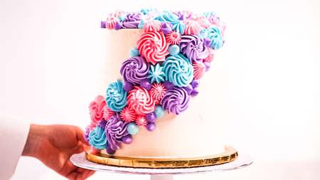 Baker tubazioni color pastello rosette di crema di burro su una torta bianca per fare una torta di unicorno.