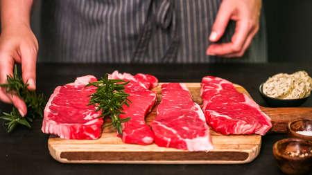 Raw New York strip steaks on a wood cutting board. Stock fotó