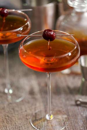 Manhattan cocktail garnished with brandied cherry.