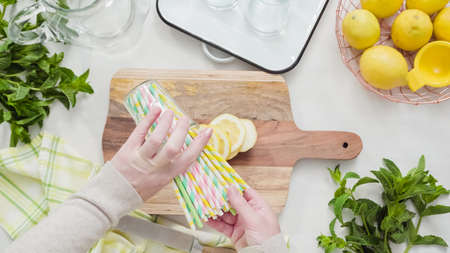 Slicing organic lemon on wood cutting board.