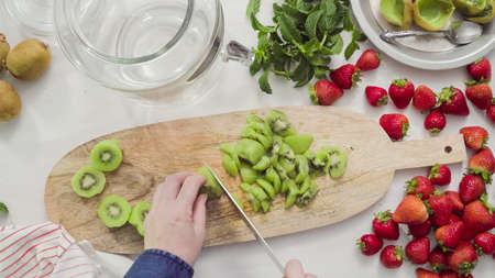 Step by step. Slicing fressh organic fruits for infused water. 版權商用圖片