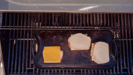 Cooking grilled cheese sandwich on outdoor gas grill.