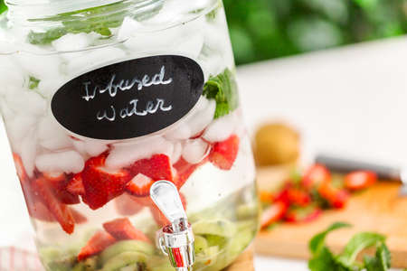 Infused water with organic strawberries, kiwi and fresh mint in glass beverage drink dispenser. 版權商用圖片