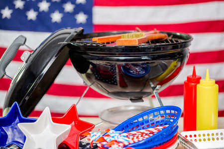 Small round charcoal grill and July 4th decorations on American flag background.
