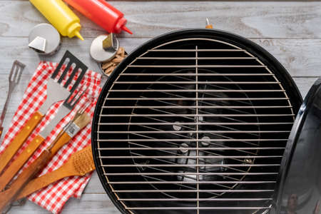 Background with BBQ cooking tools on wood background.