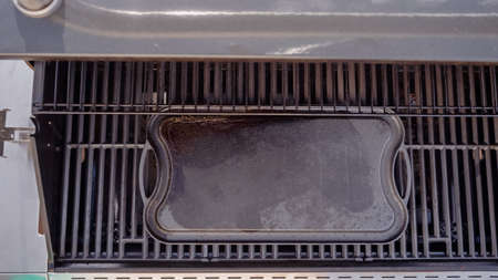 Empty cast iron griddle on outdoor gas grill. 写真素材