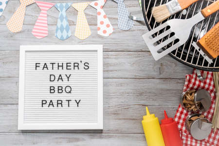 Father's Day BBQ Party sign on a white memo board with cooking tools. Imagens