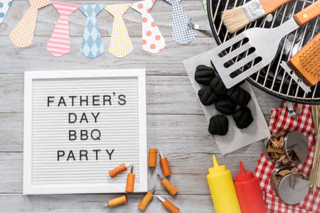 Father's Day BBQ Party sign on a white memo board with cooking tools. Stock fotó