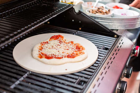 Pizza Gasgrill : Cooking pizza on outdoor gas grill. lizenzfreie fotos bilder und