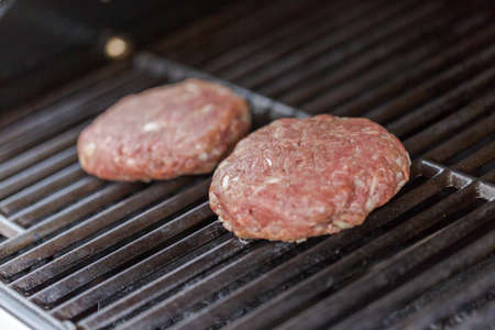 Cooking classic burgers on outdoor gas grill in the Summer.