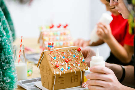 Kids decorating small gingerbread houses at the Christmas craft party. Stock Photo