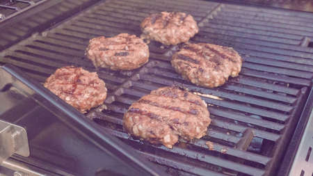 Cooking classic beef burger on outdoor gas grill. Banco de Imagens