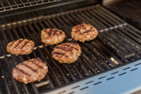 Grilling classic burgers on outdoor gas grill in the Summer. Banco de Imagens