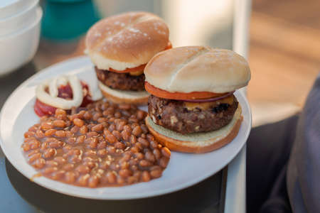 Eating dinner with classic burgers and baked beans on back patio in the Summer.
