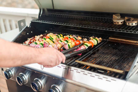 Step by step. Grilling veggie skewers and chicken kebabs on outdoor gas grill. Foto de archivo