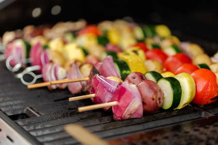 Step by step. Grilling veggie skewers and chicken kebabs on outdoor gas grill. 免版税图像