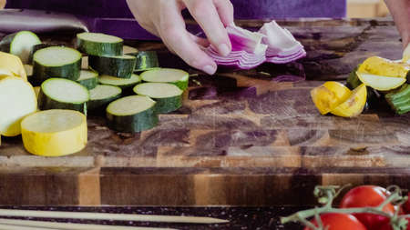 Step by step. Slicing fresh organic vegetables for veggie kebabs.