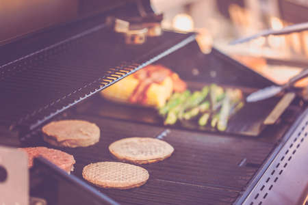 Step by step. Cooking burgers on outdoor gas grill in the Summer. Banco de Imagens