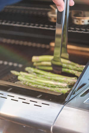 Step by step. Grilling asparagus on outdoor gas grill.