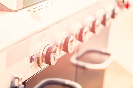 Close up of control knobs on outdoor 6 burner gas grill. Archivio Fotografico