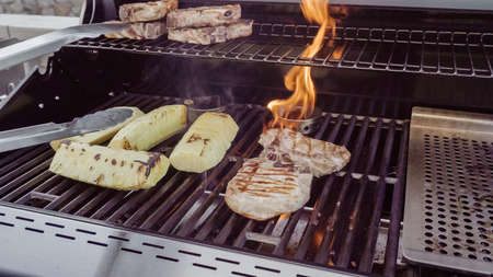 Cooking pork chops with pineapples on gas grill in the Summer. Stock Photo
