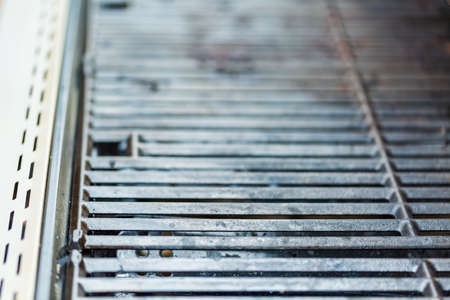 Dirty cast iron cooking grates on 6 burner outdoor gas grill.