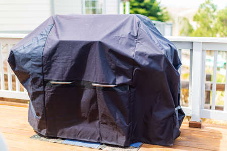 Large gas grill covered with black cover to protect from weather elements. Stock Photo
